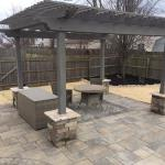 Boardwalk Pavers with driftwood inlay.  Painted pergola with bedford tumbled block pillars.