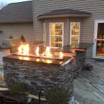 Outdoor fireplace with cultured stone finish and outdoor kitchen.